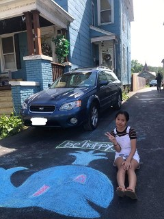 A Young Scholar poses with a picture of the whale she drew in her home's driveway.