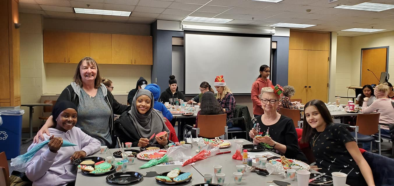 Young Scholar and their Mentors Decorating Cookies at Utica College