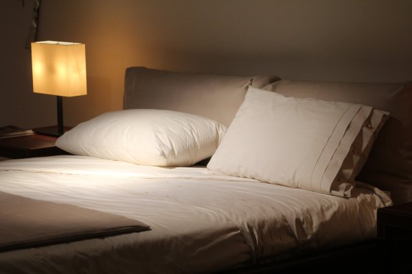 Pillows on a Bed in Dark Room with lamp light.