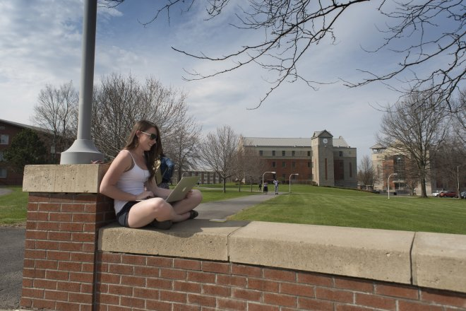 Student sitting on campus wall in Spring 060