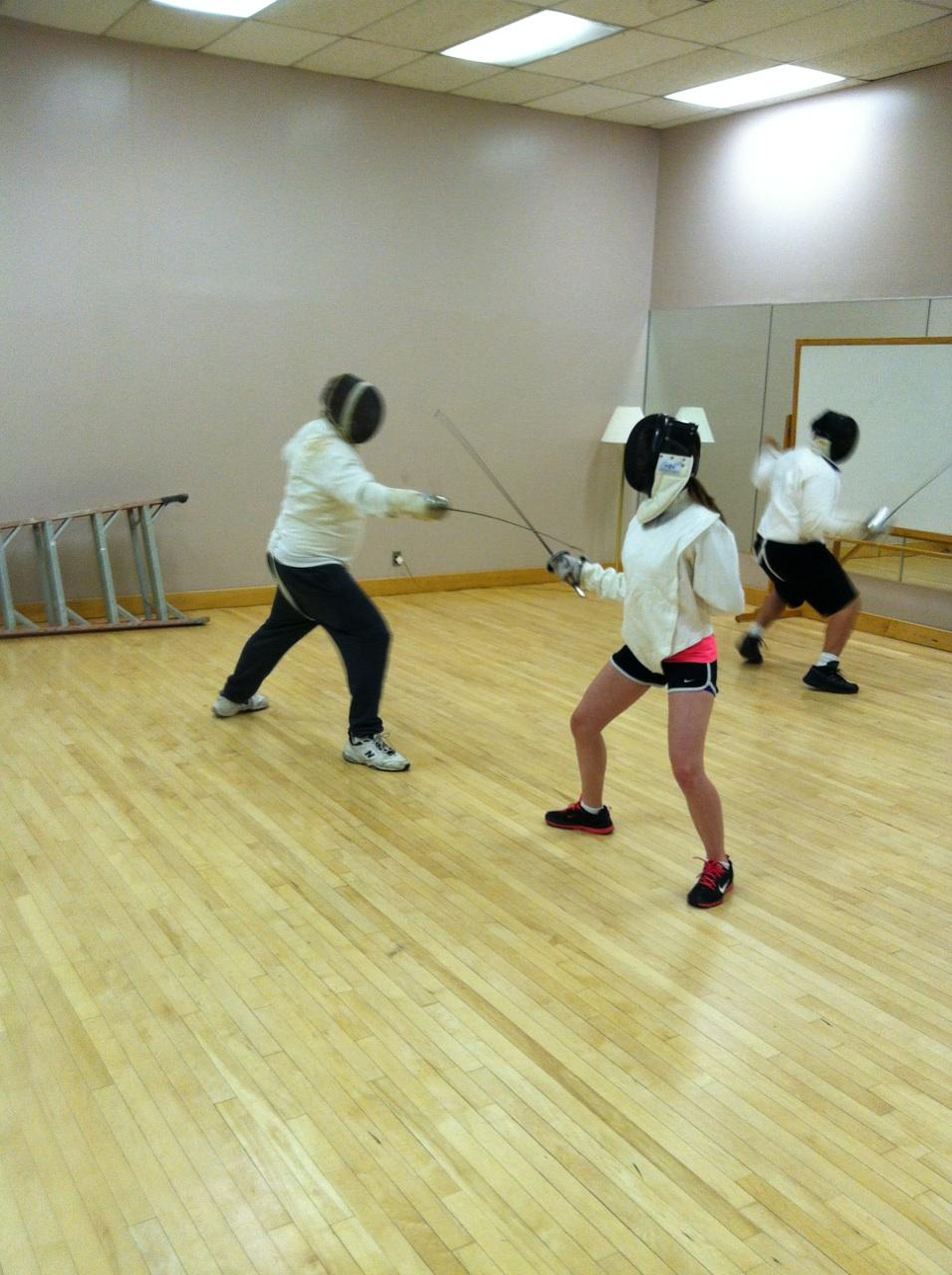 This is me fencing another student! (I am wearing the pink shirt under my vest)