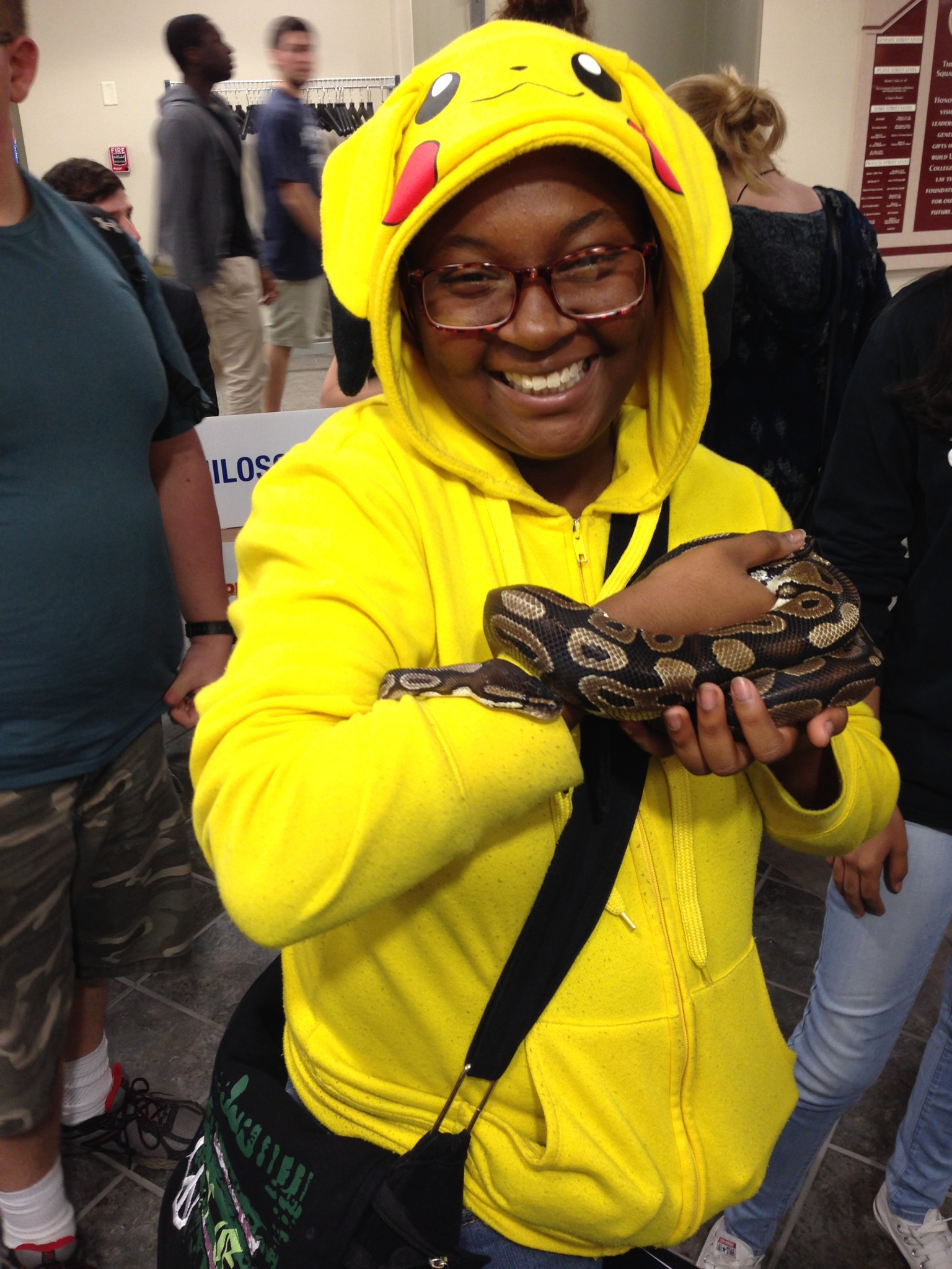 "(A student, Quinaya, holding ""Sweat-P"" the snake during the majors and minors fair.)"